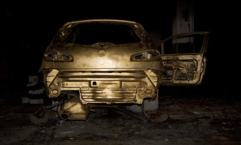 Marco Ceroni, Bling bling, 2016. Un forma dorata si staglia nel buio di uno spazio indefinito. La carcas- sa di un'auto bruciata si trasforma in oggetto altro: una pietra preziosa che popola territori di confine.